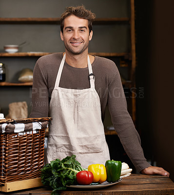 Buy stock photo Portrait of a young man standing in a kitchen with fresh vegetables in front of him