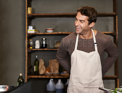Buy stock photo Shot of a young man putting on an apron before cooking a meal