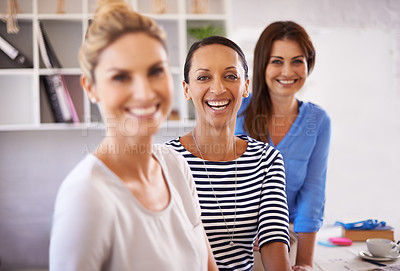 Buy stock photo Three confident young businesswomen smiling at the camera