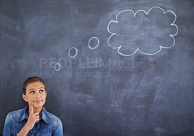 Buy stock photo Shot of a young woman  looking thoughtfully at a thought bubble