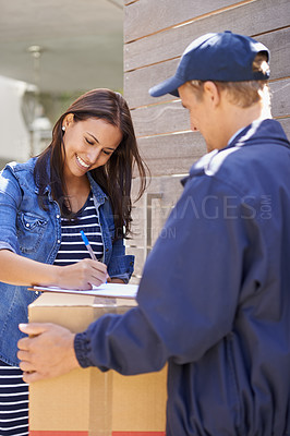 Buy stock photo A friendly delivery man delivering a package to a young woman