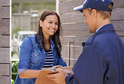 Buy stock photo Shot of a delivery man delivering a package to a young woman at her home
