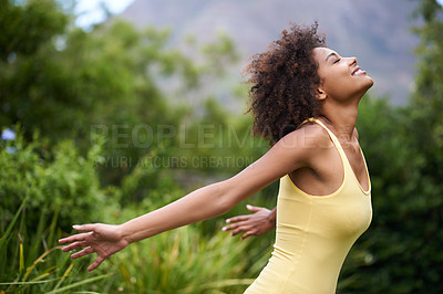 Buy stock photo Shot of a carefree and attractive young woman enjoying time in the outdoors