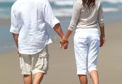 Buy stock photo Young casual couple walking on the beach. Man and woman holding hands.
