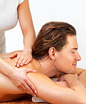 Portrait of a happy young man with eyes closed receiving shoulder massage from a female therapist