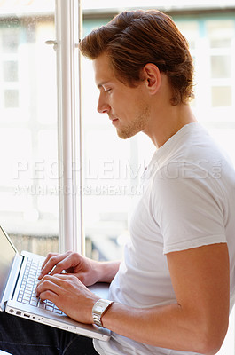 Buy stock photo A student working hard on his laptop by his windowsill.