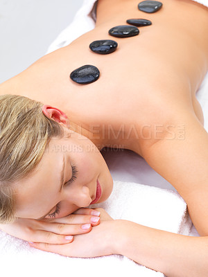Buy stock photo Hot stone massage in the day spa - Portrait of a beautiful young girl at the day spa with black stones on her bare back