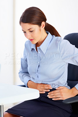 Buy stock photo Young female executive holding her belly in pain
