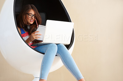 Buy stock photo Cute young girl sitting in an egg chair using laptop and taking notes