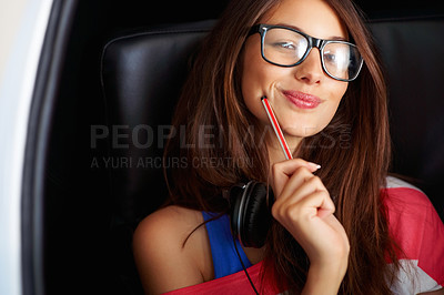 Buy stock photo Closeup of a young girl wearing glasses sitting holding a pen and giving you a cute smile