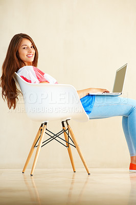 Buy stock photo Portrait of pretty young girl sitting on chair using laptop and giving you an attractive smile