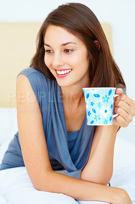 Buy stock photo Young woman with an attractive smile holding cup of coffee and looking away