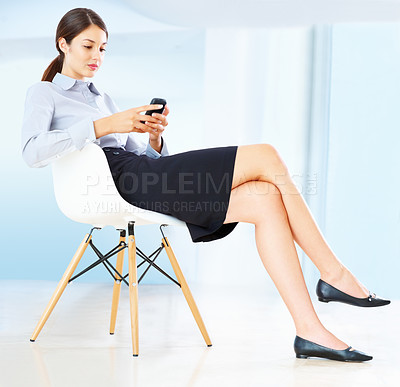 Buy stock photo Full length of an attractive young business woman sitting on chair and using mobile phone