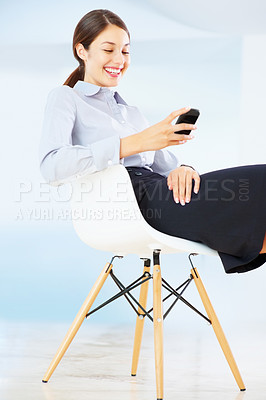 Buy stock photo Beautiful young business woman reading funny text message on mobile phone and smiling