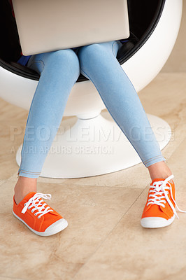 Buy stock photo Low section of girl in jeans and canvas shoes sitting on an egg chair using laptop