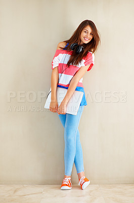Buy stock photo Full length of beautiful young girl standing near wall and holding laptop with both hands