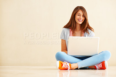 Buy stock photo Full length of cute young woman sitting on the floor using laptop