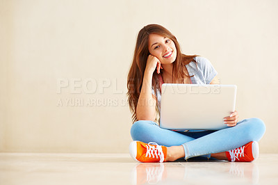 Buy stock photo Full length of attractive young female sitting on the floor using laptop next to copyspace