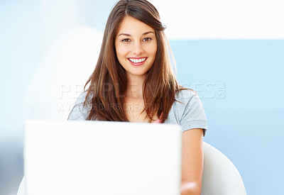 Buy stock photo Portrait of beautiful young woman sitting on chair using laptop and smiling
