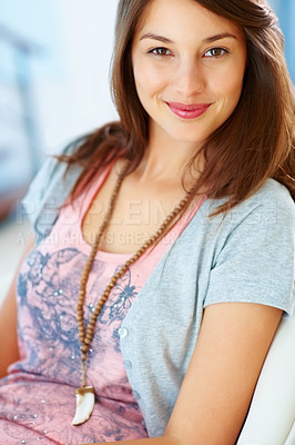 Buy stock photo Portrait of young woman sitting on chair and giving you cute smile
