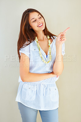 Buy stock photo Portrait of happy young woman pointing on plain background