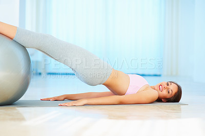 Buy stock photo Happy young woman utilizing fitness ball to workout