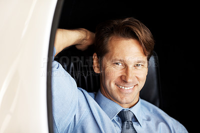 Buy stock photo Portrait of a happy young male entrepreneur relaxing on chair and smiling