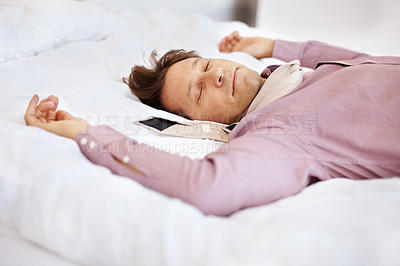Buy stock photo Portrait of a tired young businessman comfortably sleeping in his bed
