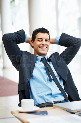 Buy stock photo Executive leaning back in chair with hands on back of head