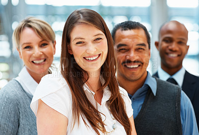Buy stock photo Focus on young female executive with team in background