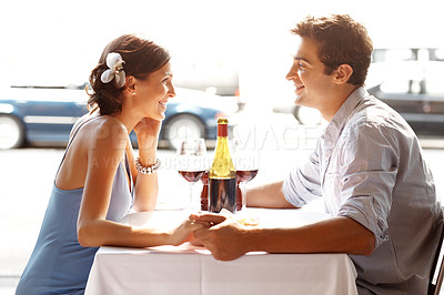 Buy stock photo Romantic young couple sitting in a restaurant holding their hands