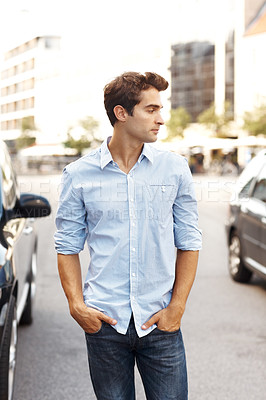 Buy stock photo Handsome young man standing on the street with his hands in pocket looking away