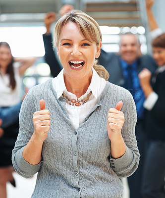 Buy stock photo Enthusiastic female executive holding two thumbs up with excited colleagues in background