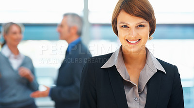 Buy stock photo Pretty young executive with colleagues discussion in background
