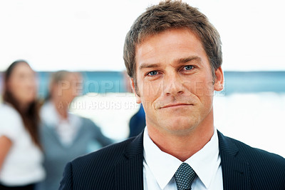 Buy stock photo Closeup view of handsome executive with colleagues in background