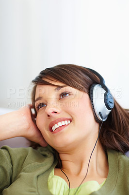 Buy stock photo Cute young woman hearing songs on mp3 player