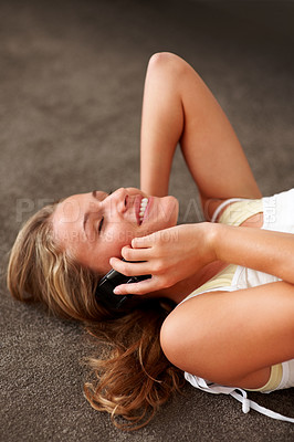Buy stock photo Sweet young woman enjoying conversation on mobile phone while lying on the floor