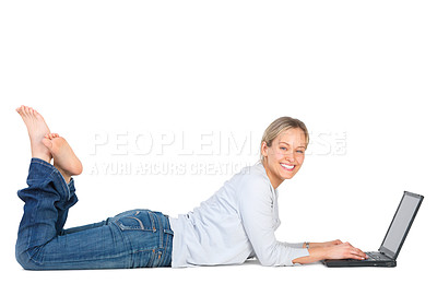 Buy stock photo Full length shot of an attractive young woman lying on the studio floor using a laptop