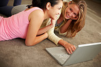 Happy young women working together on laptop