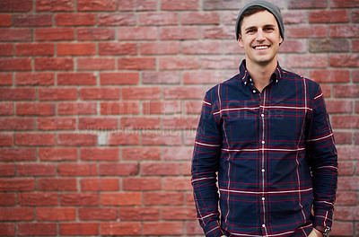 Buy stock photo Portrait of a handsome young man standing in front of a face brick wall