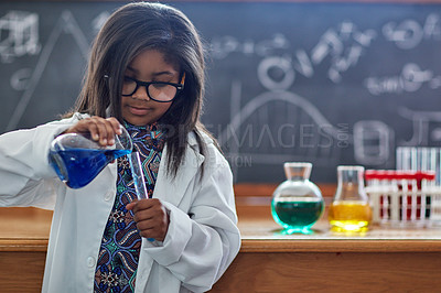 Buy stock photo Shot of a little girl in a lab coat doing a science experiment in a lab