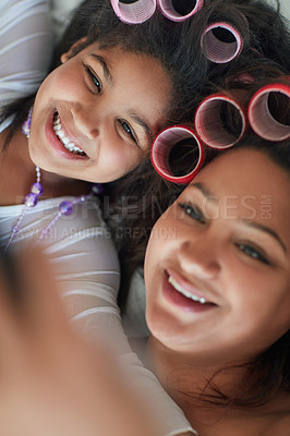 Buy stock photo Shot of a mother and her little girl taking a selfie together while wearing curlers