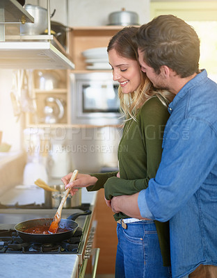 Buy stock photo Shot of an affectionate young couple preparing dinner together at the stove in their kitchen
