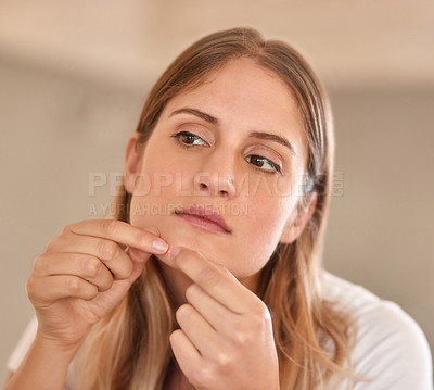 Buy stock photo Cropped shot of a young woman squeezing a pimple on her face