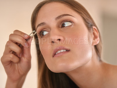 Buy stock photo Cropped shot of a young woman plucking her eyebrows with a pair of tweezers