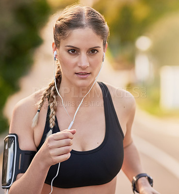 Buy stock photo Shot of an attractive young woman listening to music while out for her morning run