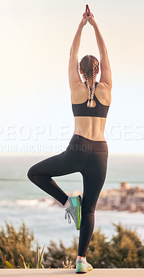 Buy stock photo Rearive shot of an attractive young woman doing yoga outdoors