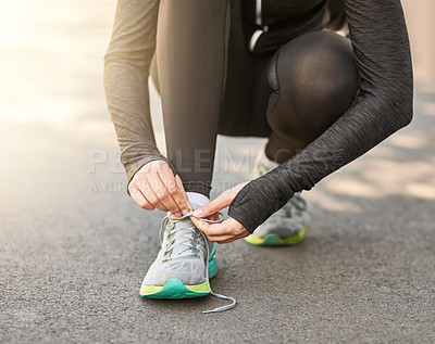 Buy stock photo Shot of an unrecognizable young woman tying her laces before a morning run