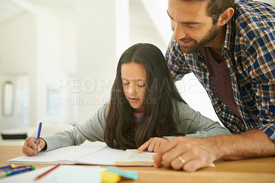 Buy stock photo Shot of a father helping his daughter with her homework