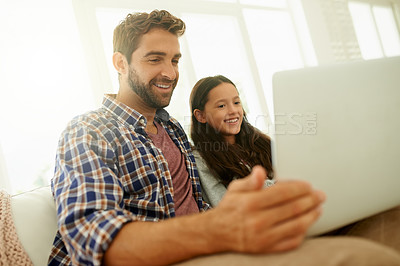 Buy stock photo Shot of a father and daughter using a laptop together